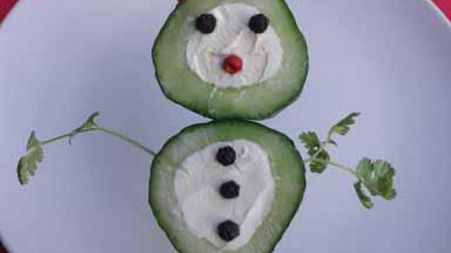 Gezond borrelhapje: komkommer mannetje gevuld met roomkaas.