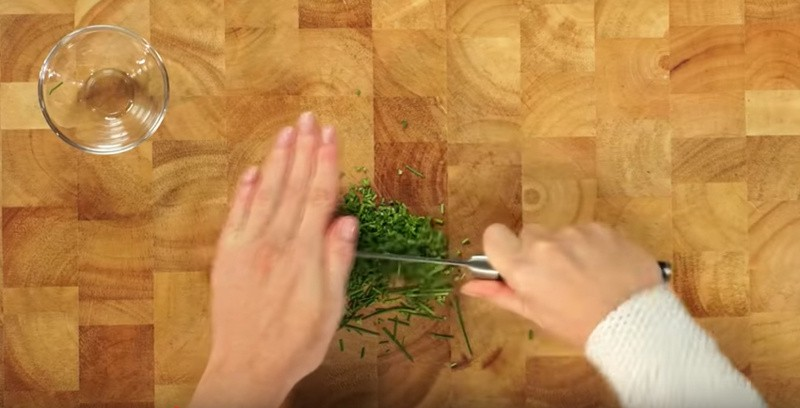 De knoflook pellen en de kruiden fijnhakken