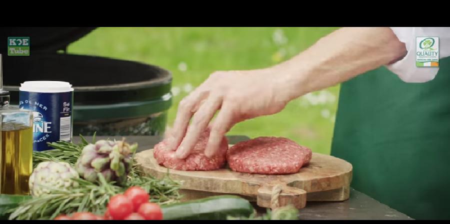 De hamburgers op de BBQ leggen