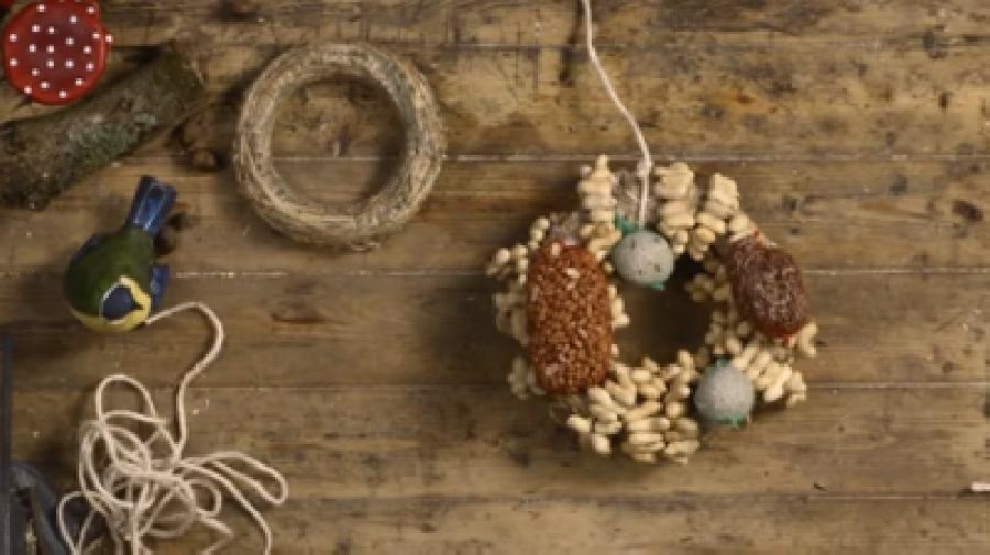 De krans verder versieren met vetbollen en ander vogelvoer