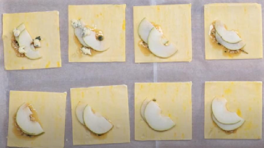 Het bladerdeeg bedekken met het honingmengsel, de peer en de kaas