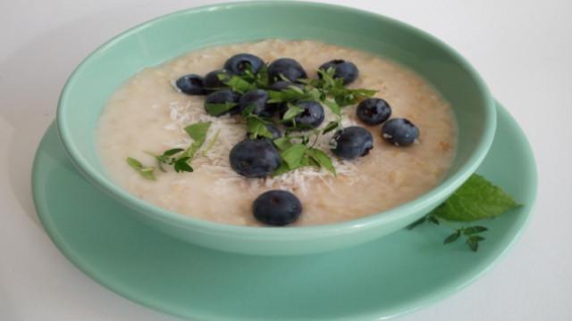 Gezond ontbijt: havermoutpap met blauwe bessen en verse kruiden.