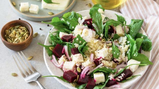 'Bloemkoolcouscous' salade met rode bieten, kastanjechampignons en sinaasappeldressing.